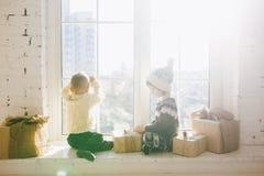 Les enfants frère et soeur de l'âge préscolaire s'asseyent par la fenêtre un jour ensoleillé de Noël et jouent avec des boîtes de Photos libres de droits