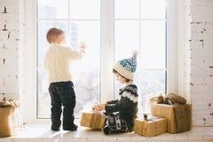 Les enfants frère et soeur de l'âge préscolaire s'asseyent par la fenêtre un jour ensoleillé de Noël et jouent avec des boîtes de Photo libre de droits