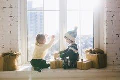 Les enfants frère et soeur de l'âge préscolaire s'asseyent par la fenêtre un jour ensoleillé de Noël et jouent avec des boîtes de Photo stock