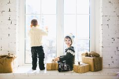 Les enfants frère et soeur de l'âge préscolaire s'asseyent par la fenêtre un jour ensoleillé de Noël et jouent avec des boîtes de Image libre de droits