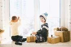 Les enfants frère et soeur de l'âge préscolaire s'asseyent par la fenêtre un jour ensoleillé de Noël et jouent avec des boîtes de Photographie stock