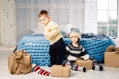 Les enfants frère et soeur s'asseyent sur le plancher dans la chambre à coucher près du lit avec des cadeaux sur le fond du décor Photo stock