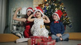 Les enfants gais utilisent des chapeaux du père noël sur leurs têtes Nuit de nouvelle année au pied de l'arbre de Noël banque de vidéos