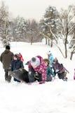 Les enfants glissant sur la neige glisse en hiver russe Image libre de droits