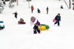 Les enfants glissant sur la neige glisse en hiver russe Photographie stock
