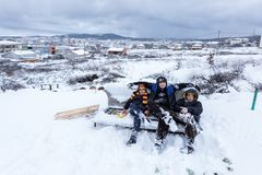 Les enfants glissent sur la neige dans le style de vieille école avec le bois dur Images libres de droits
