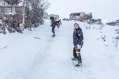 Les enfants glissent sur la neige dans le style de vieille école avec le bois dur Images stock