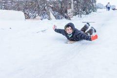 Les enfants glissent sur la neige dans le style de vieille école avec le bois dur Image stock