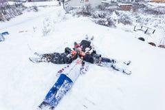 Les enfants glissent sur la neige dans le style de vieille école avec le bois dur Photos stock