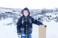 Les enfants glissent sur la neige dans le style de vieille école avec le bois dur Photographie stock