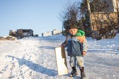 Les enfants glissent sur la neige dans le style de vieille école avec le bois dur Photographie stock libre de droits
