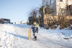 Les enfants glissent sur la neige dans le style de vieille école avec le bois dur Photo libre de droits