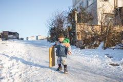 Les enfants glissent sur la neige dans le style de vieille école avec le bois dur Image libre de droits
