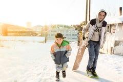 Les enfants glissent sur la neige dans le style de vieille école avec le bois dur Photos libres de droits
