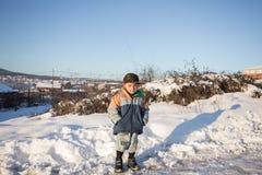 Les enfants glissent sur la neige dans le style de vieille école avec le bois dur Photo stock