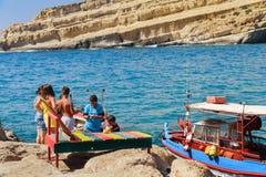 Les enfants grecs sont les poissons contagieux à la côte de la ville de Matala sur l'île de Crète, Grèce Photos stock