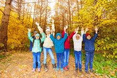 Les enfants groupent avec des bras se tenant dans la rangée ensemble Photo stock