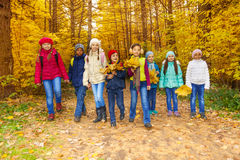 Les enfants groupent avec des feuilles d'érable que les groupes marchent ensemble Photographie stock