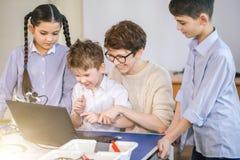 Les enfants heureux apprennent la programmation utilisant des ordinateurs portables sur les classes hors programme images stock