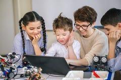 Les enfants heureux apprennent la programmation utilisant des ordinateurs portables sur les classes hors programme photo libre de droits