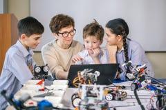 Les enfants heureux apprennent la programmation utilisant des ordinateurs portables sur les classes hors programme images libres de droits