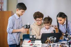 Les enfants heureux apprennent la programmation utilisant des ordinateurs portables sur les classes hors programme image libre de droits