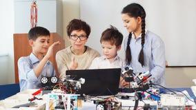 Les enfants heureux apprennent la programmation utilisant des ordinateurs portables sur les classes hors programme banque de vidéos
