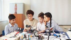Les enfants heureux apprennent la programmation utilisant des ordinateurs portables sur les classes hors programme
