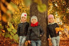 Les enfants heureux d'amis du portrait trois en automne garent - l'enfant, le leisute et l'amitié Photographie stock