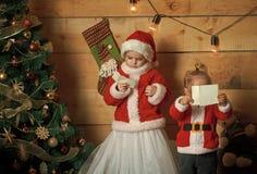 Les enfants heureux de Noël à l'arbre de nouvelle année ont lu la lettre de souhait photos libres de droits