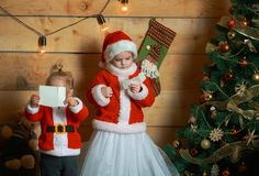 Les enfants heureux de Noël à l'arbre de nouvelle année ont lu la lettre de souhait photographie stock libre de droits