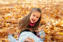 Les enfants heureux en automne garent le mensonge sur des feuilles Photographie stock libre de droits