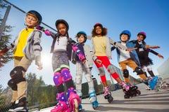 Les enfants heureux faisant du roller avec des mains aiment des ailes Photographie stock