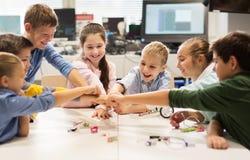 Les enfants heureux faisant le poing se cognent à l'école de robotique Photographie stock