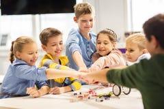 Les enfants heureux faisant le poing se cognent à l'école de robotique Images stock