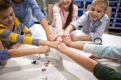 Les enfants heureux faisant le poing se cognent à l'école de robotique Photographie stock libre de droits