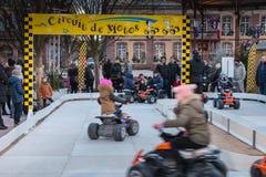 Les enfants heureux font le quadruple faisant du vélo sur la glace dans Noël mars photo libre de droits