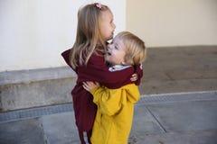 Les enfants heureux garçon et fille se sont habillés dans la caresse de hoodie, montrant l'amour l'un pour l'autre photographie stock libre de droits