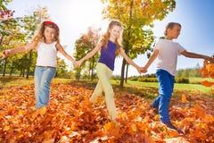 Les enfants heureux jouent tenant des mains en parc Photographie stock