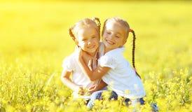 Les enfants heureux jumelle des soeurs embrassant en été sur la nature Images stock