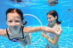Les enfants heureux nagent dans la piscine sous l'eau, des filles nageant Image libre de droits