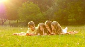 Les enfants heureux poussent des feuilles par un livre dans le jardin sur la pelouse par jour d'été clips vidéos
