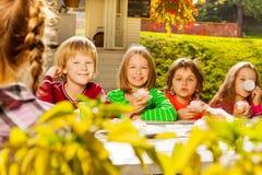 Les enfants heureux s'asseyent au thé potable de table en bois Photos stock