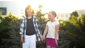 Les enfants heureux se tiennent ensemble Le garçon et la fille ont l'amusement dehors clips vidéos