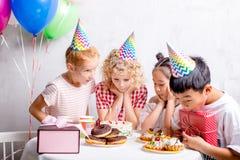 Les enfants heureux sont prêts à goûter le gâteau d'anniversaire photo libre de droits