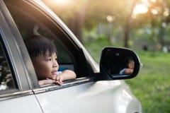 Les enfants heureux voyagent en la voiture, coups d'oeil de petit garçon hors de la voiture dans le coucher du soleil photo stock