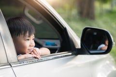 Les enfants heureux voyagent en la voiture, coups d'oeil de petit garçon hors de la voiture dans le coucher du soleil images stock