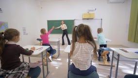 Les enfants instruisant, jeune femelle de professeur près du tableau noir conduit la leçon cognitive pour de petits enfants au bu banque de vidéos