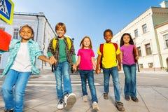 Les enfants internationaux portent des sacs et marchent dans la rangée Photo stock