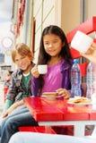 Les enfants internationaux s'asseyant en café de ville et mangent Image stock